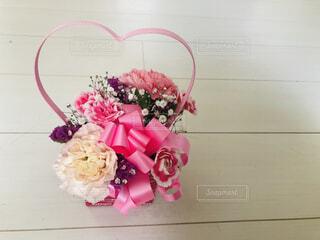 持ち手がピンクのハート型のカーネーションの花束の母の日デザインのギフトボックスの写真・画像素材[4402173]