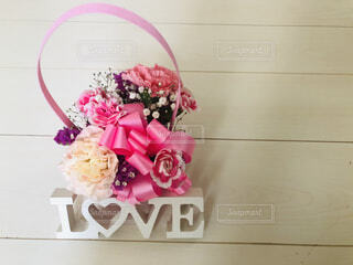 白い木材の上にカーネーションの花束とLOVEメッセージの写真・画像素材[4402513]