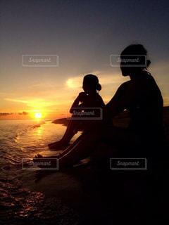 バック グラウンドで夕焼けのビーチに座っている男の写真・画像素材[768844]