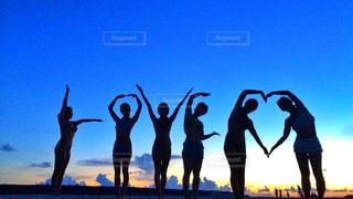日没の前に立っている人々 のグループの写真・画像素材[1018031]