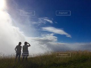 草で覆われた丘の上に立っている人の写真・画像素材[1115414]