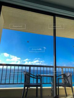 窓の前に座っている椅子の写真・画像素材[3253837]