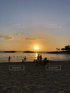 水の体の近くのビーチで人々のグループの写真・画像素材[3395308]