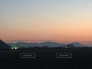 背景の山が付いている水の体に沈む夕日の写真・画像素材[960992]