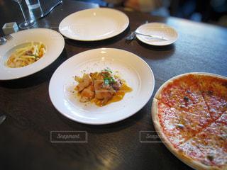 近くにテーブルの上のピザのプレートのアップの写真・画像素材[923240]