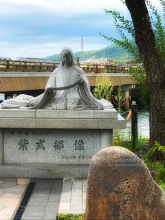 銅像の前でベンチに座っている人の写真・画像素材[929208]