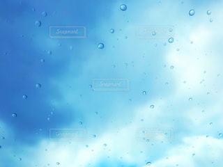 空とガラス越しの雨粒の写真・画像素材[1089924]