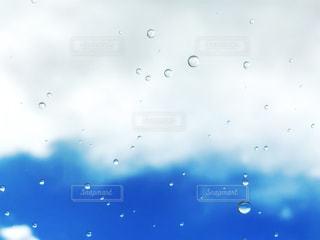 雨雲と青空を背景に水玉の雨粒の写真・画像素材[1090395]