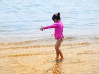 ビーチの上を歩く少女の写真・画像素材[1385338]
