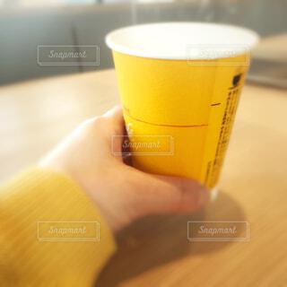 コーヒーの入った紙コップの手持ちフォトの写真・画像素材[4302108]