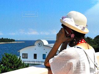女性,海,建物,夏,木,緑,赤,白,青空,青,帽子,葉,スマホ,電話