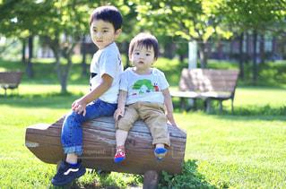 公園のベンチに座っている少年の写真・画像素材[815987]