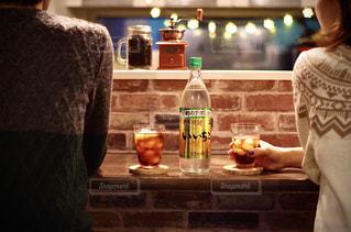 テーブルの上のワインのボトルの隣に立っている人の写真・画像素材[2728620]