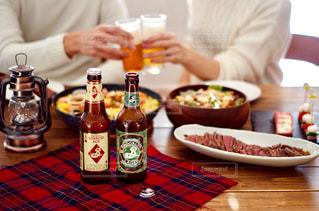 食べ物の皿を持ってテーブルに座っている人の写真・画像素材[2816444]