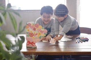 窓の前の机に座っている少年の写真・画像素材[2887508]