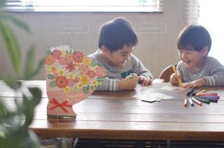 テーブルに座っている若い男の子の写真・画像素材[2887507]