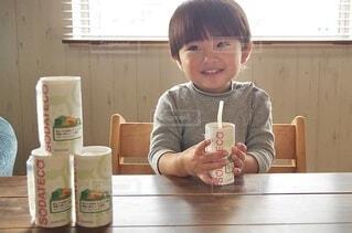 コーヒーを飲みながらテーブルに座っている少年の写真・画像素材[3932213]