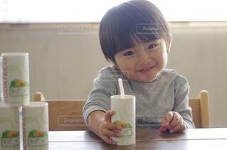 コーヒーを飲みながらテーブルに座っている小さな男の子の写真・画像素材[3932220]