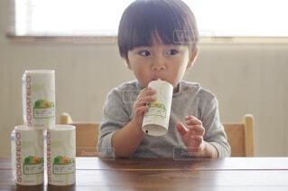 食べ物を食べるテーブルに座っている小さな男の子の写真・画像素材[3932222]