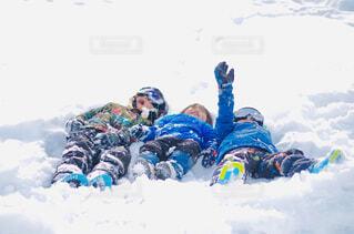 雪に覆われた斜面の下にスノーボードに乗っている人の写真・画像素材[4080689]