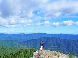 青空のもと壮大な山々を眺めるカップルの写真・画像素材[4503862]