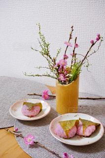 テーブルの上の花の花瓶をのせた白プレートの写真・画像素材[1823164]