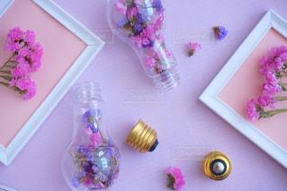 テーブルの上にピンクの花を詰めた花瓶の写真・画像素材[2121308]
