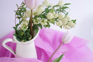 テーブルの上に紫色の花を詰めた花瓶の写真・画像素材[2121320]