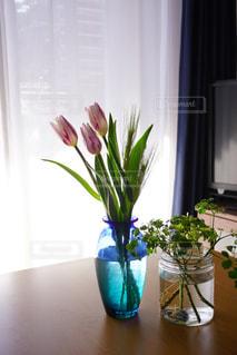 テーブルの上に座っている花で満たされた花瓶の写真・画像素材[2141333]