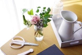 テーブルの上にコーヒーと花瓶1本の写真・画像素材[2733554]