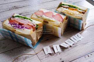 木製のテーブルの上に座っているサンドイッチの写真・画像素材[4355733]