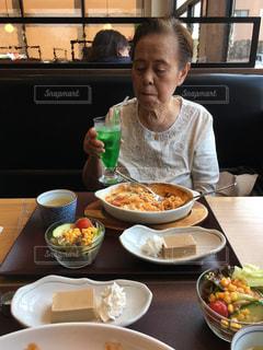 食品のプレートをテーブルに座っている女性 - No.722881