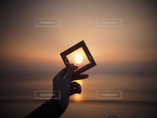 バック グラウンドで夕日を持つ人の写真・画像素材[1224874]