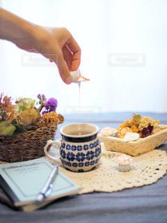 食物と一緒にテーブルに座っている女性の写真・画像素材[1262475]