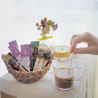 一杯のコーヒーをテーブルに座っている女性の写真・画像素材[1293334]