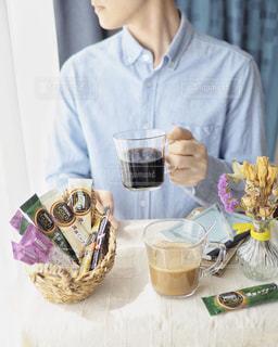 テーブルの上のコーヒー カップを保持している人の写真・画像素材[1293438]