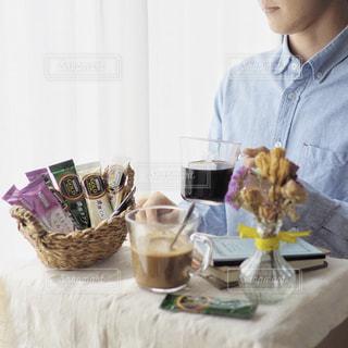 食物と一緒にテーブルに座って人の写真・画像素材[1293462]
