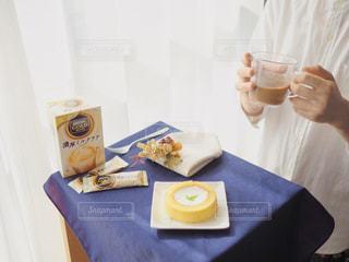 テーブルの上のコーヒー カップを持つ手の写真・画像素材[1308633]