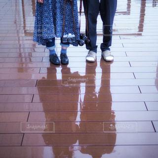 2人,カメラ,カップル,雨,屋外,足元,テラス,反射,床,人物,人,リフレクション,梅雨,天気,雨の日,履物