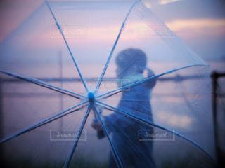 夕焼けに包まれる傘越しの女性の写真・画像素材[2249082]