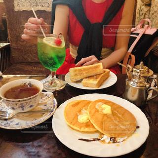 食べ物の皿を持ってテーブルに座っている女性の写真・画像素材[2297287]