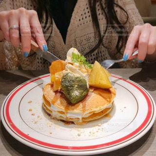 ナイフで食べ物の皿を持ってテーブルに座っている女性の写真・画像素材[2301885]