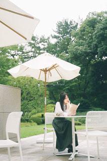 傘を持ってテーブルに座っている人の写真・画像素材[2495799]
