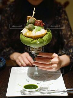 食べ物の皿を持ってテーブルに座っている人の写真・画像素材[2698761]