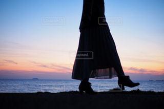 夕日の前の浜辺に立つ人の写真・画像素材[2702954]