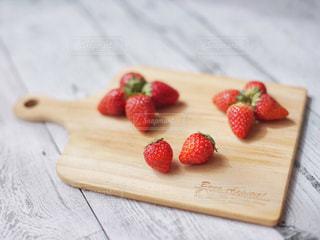 木製のまな板の上に座っているイチゴの写真・画像素材[3149781]