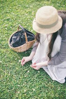 野原に座って花を摘む女性 縦バージョンの写真・画像素材[4465814]
