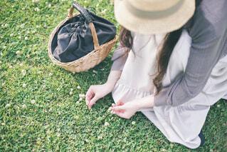 野原に座って花を摘む女性 横バージョンの写真・画像素材[4465816]
