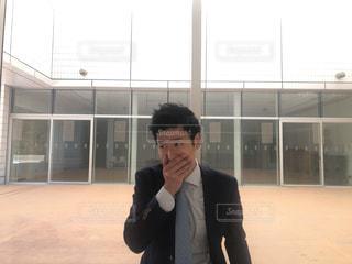 建物の前に立っているスーツの男の写真・画像素材[1016340]