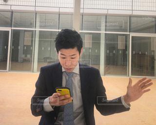 携帯電話を保持している男の写真・画像素材[1019810]